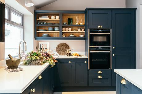 Contemporary kitchen design with navy blue cupboards and brass handles