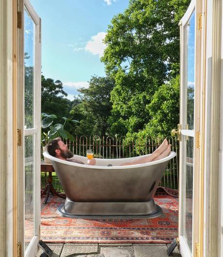 man sat in a bath on balcony