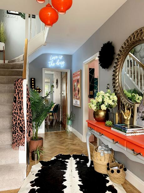 Eclectic hallway inspiration - pale gray and bright orange color palette with cowhide rug and herringbone floor