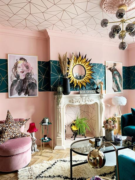 Pink and teal eclectic living room with geometric wallpaper and velvet furniture