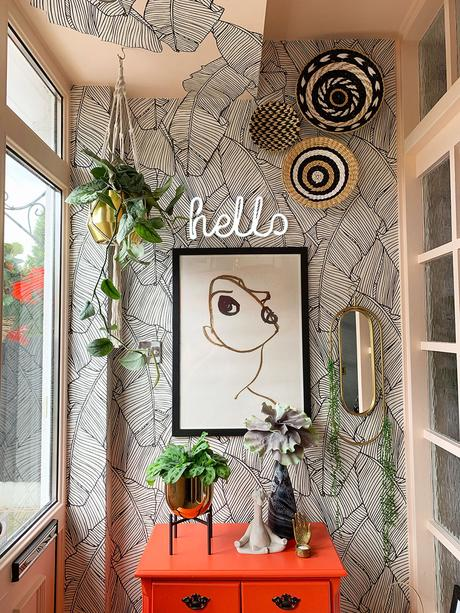 Quirky porch decor inspiration with orange cabinet and monochrome patterned wallpaper