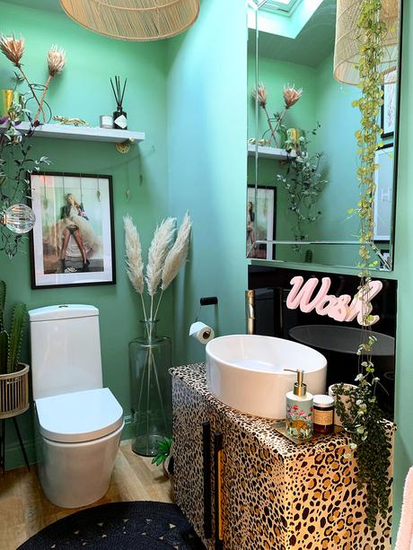 Quirky bathroom decor. Green and black color palette with leopard print wash stand