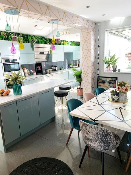 Pink and blue modern kitchen with colourful glass lights and geometric wallpaper