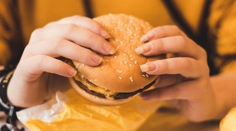 Image: Person Holding a Cheeseburger | Photo by Christian Wiediger on Unsplash