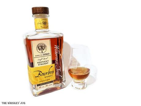White background tasting shot with the Wilderness Trail Wheated Bourbon bottle and a glass of whiskey next to it.