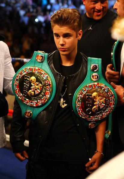 Justiin Bieber wearing two title belts at Miguel Cotto fight along with a Golden Koi Fish necklace worth $20,000.