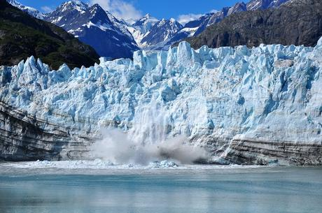 The front of a glacier breaking away and falling into the sea.