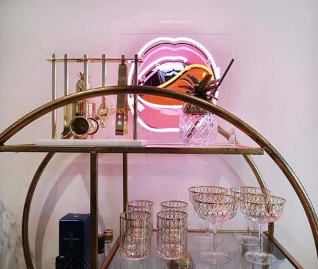 Pink neon lips styled beautifully on our gold round drinks trolley