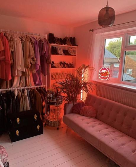 Glamorous dressing room decor with pink velvet sofa and pink neon lights