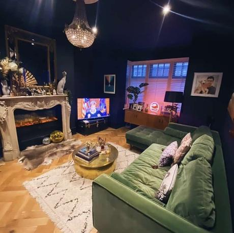 Navy blue living room with green velvet sofa and quirky home accessories