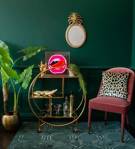 Gold round drinks trolley styling inspiration with neon ligh, gold rock on hand and cool barware