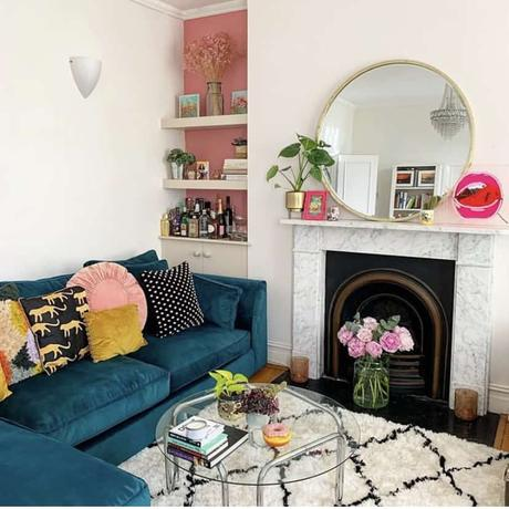 Pink and white living room inspiration with lush house plants, navy blue velvet sofa and berber style rug