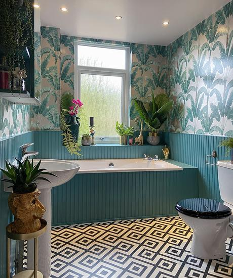 Tropical patterned wallpaper with teal panelling and patterned monochrome vinyl flooring