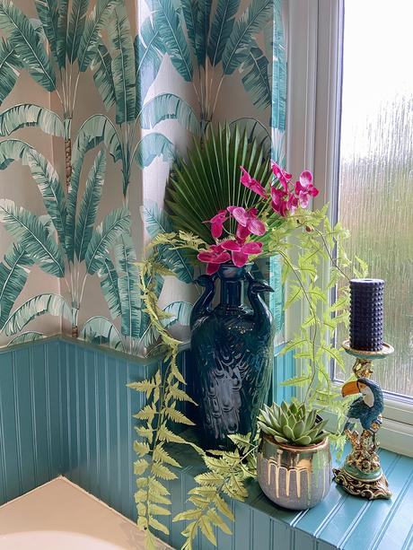 Tropical patterned wallpaper with artificial flowers and toucan candle holder to give a jungle feel