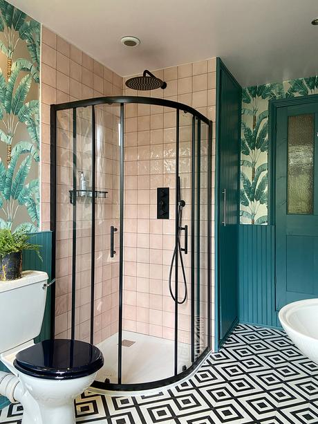 Tropical bathroom decor. Black shower enclosure with pink tiles, tropical wallpaper and monochrome patterned vinyl flooring