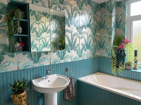 Tropical patterned wallpaper with artificial house plants and gold monkeys to give a jungle feel