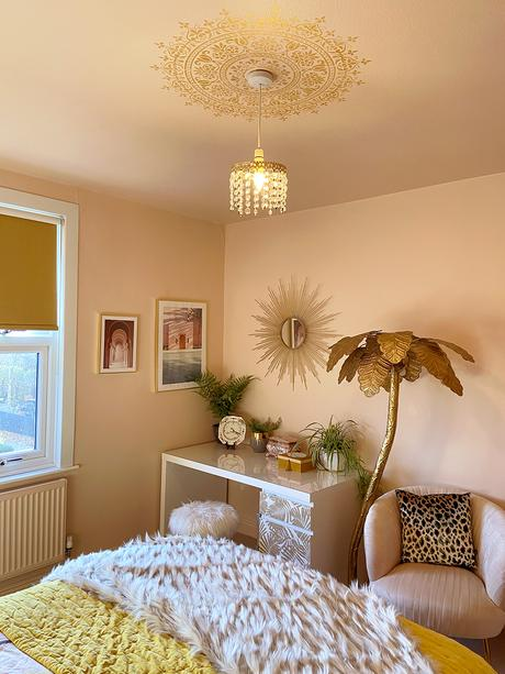 Gold ceiling medallion stencil in blush pink bedroom with gold accessories