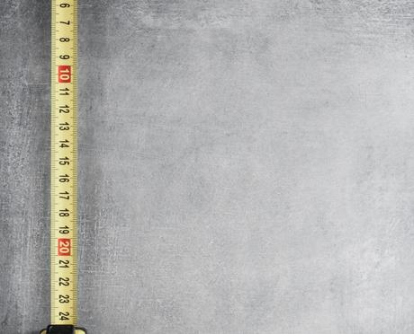 Tape measure and pencil on gray background
