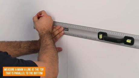 hand drawing a line on the wall with a pencil