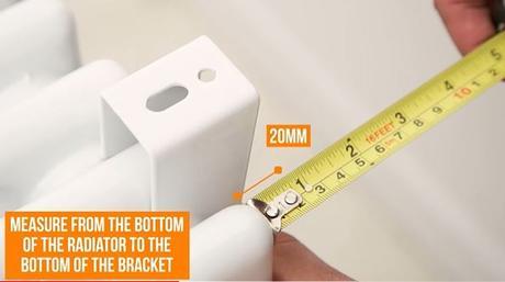 hand measuring a radiator bracket