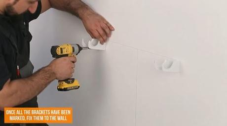 man drilling a hole into a wall