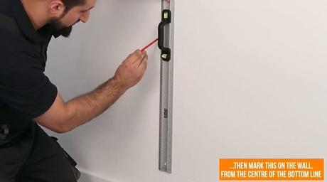 man marking a line on a wall with a pencil