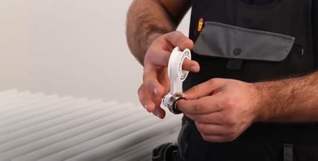 hands wrapping ptfe tape around a radiator valve