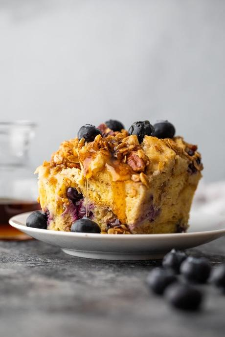side view of a piece of french toast casserole on a white plate with blueberries on top and syrup behind it