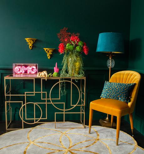 Gold console table styled with pink neon, colourful faux flowers and mustard yellow velvet chair.