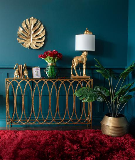 Moody blue living room with gold console table and quirky giraffe lamp