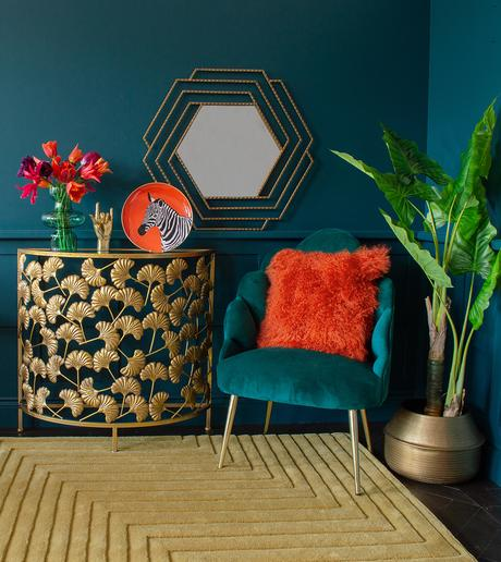 Gold ginkgo leaf console table with mustard wool rug and pops of bright orange home accessories
