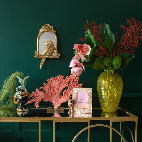 Feminine, pink and gold home decor with vintage style parrot mirror and pin coral on stand