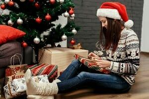 Girl under a christmas tree wearing thick socks and a jumper