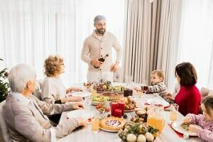 a family sat around the dinner table at christmas