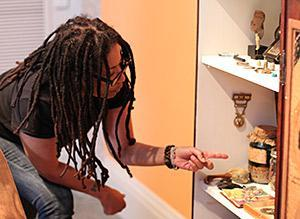 Renee Stout looks into art piece