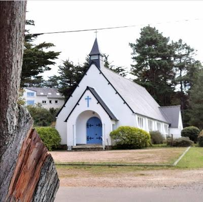 Photograph of a small white chapel with steeply pitched gray roof and spire; its blue front door is sheltered by a porch which also has a steeply-pitched roof. In the foreground is the trunk of a tree.