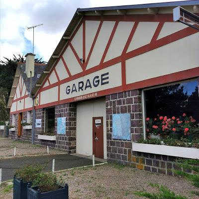 Photograph of a long building with a stone ground floor and two half-timbered gables, painted cream with rust-red woodwork. A sign says 'Garage'.