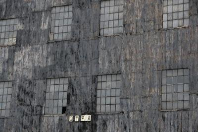 Detail of the front gable wall. The photograph shows a section of corrugated iron, pierced with windows. Each window is subdivided by metal frames into numerous small, rectangular pains. Towards the bottom of the image, a sign shows the letters O, Y and PIA.