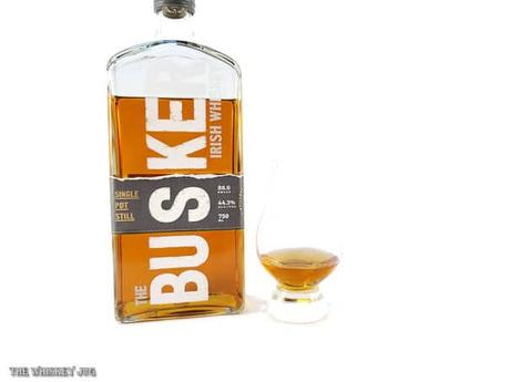 White background tasting shot with the Busker Single Pot Still bottle and a glass of whiskey next to it.