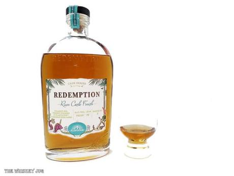 White background tasting shot with the Redemption Rum Cask Finish Whiskey bottle and a glass of whiskey next to it.