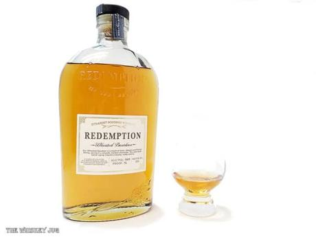 White background tasting shot with the Redemption Wheated Bourbon bottle and a glass of whiskey next to it.
