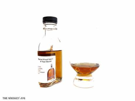 White background tasting shot with the Redemption 9 Year Barrel Proof Bourbon bottle and a glass of whiskey next to it.