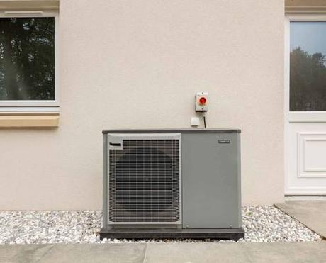 Air source heat pump fitted outside near patio