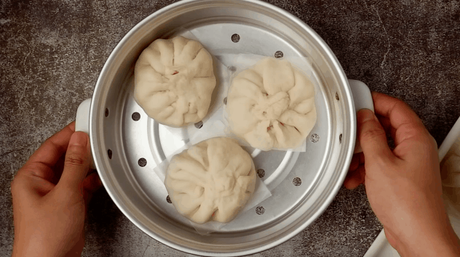 Siopao buns on wax paper ready to be steamed