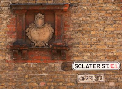 Photograph of a section of brick wall. In the left half of the picture is a fancy cream tablet with leaf and flower decoration, cracked and with 'SCLATER STREET' barely legible; it is surrounded by a red brick frame. To the right, in the lower part of the image, are two smaller rectangular signs. The upper one says 'SCLATER ST. E.1.'; the lower one, smaller and a little battered, is in Bengali script.