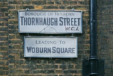 A photograph of a brick wall with a black, metal drainpipe and large bracket on the right-hand edge. There are two signs, similar in age and style. The upper one has a cracked white background and says 'BOROUGH OF HOLBORN' in red, 'THORNHAUGH STREET' in black, and 'W.C.1' in red italics. The lower one has black text reading 'LEADING TO WOBURN SQUARE'