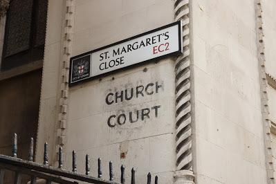 Photograph of a pale stone wall with carved decoration. A modern street sign with a City of London crest says 'ST. MARGARET'S CLOSE EC2'. Below, painted directly onto the wall, are the words 'CHURCH COURT' in fading black paint.