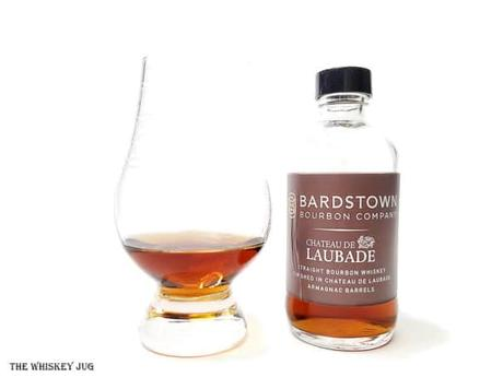 White background tasting shot with the Bardstown Bourbon Laubade Armagnac Finish bottle and a glass of whiskey next to it.