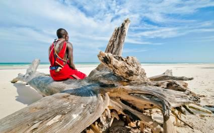 Man from the Maasai tribe sits on the shore of the Indian ocean