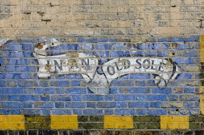 Photograph showing a detail from a Redferns ghost sign: a scroll with the words 'In an old sole' on a blue background, painted onto a brick wall.
